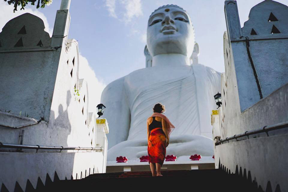 photo of woman in front of buddha statue
